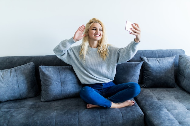 Happy young woman sitting on sofa with phone and having video call at home Free Photo