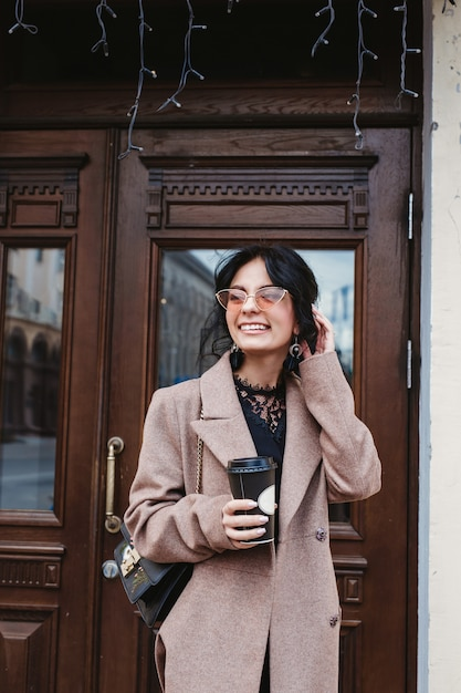Happy young woman smiling in a trendy coat and sunglasses with a coffee walk in the city Premium Photo