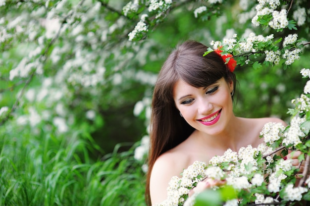 Happy young woman in a spring park smelling the flowers Premium Photo
