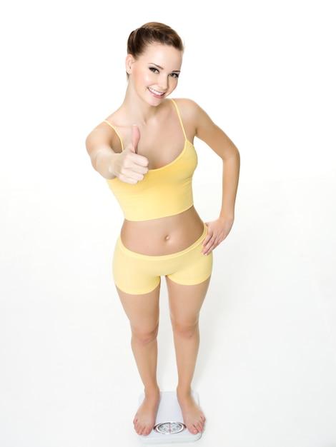 幸せな若い女立っているスケールし、白で隔離される親指を示しています。ハイアングル 無料写真
