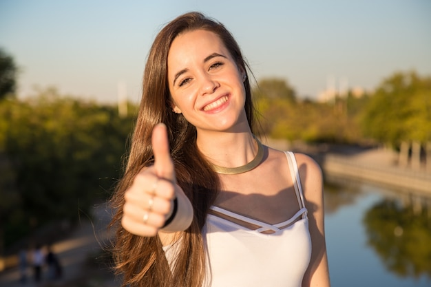 Happy young woman standing in park on sunny day and gesturing thumb up. Premium Photo