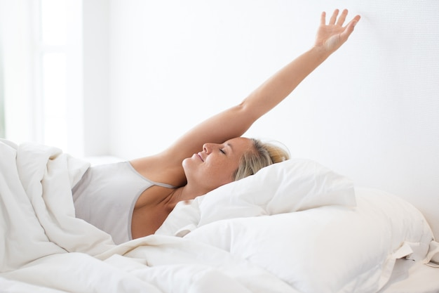 Happy young woman stretching in bed after sleep Free Photo