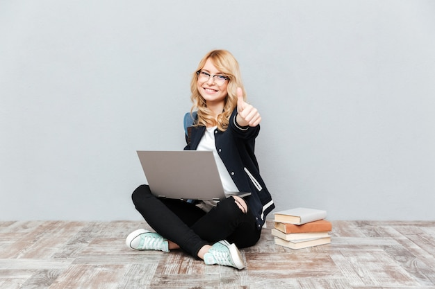 Happy young woman student using laptop computer. Free Photo