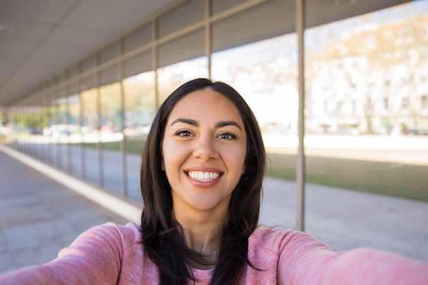 Happy young woman taking selfie photo outdoors Free Photo