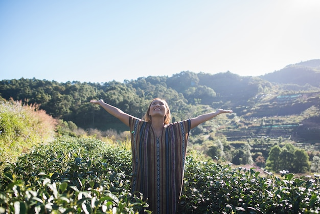 Happy young woman on tea plantation Free Photo