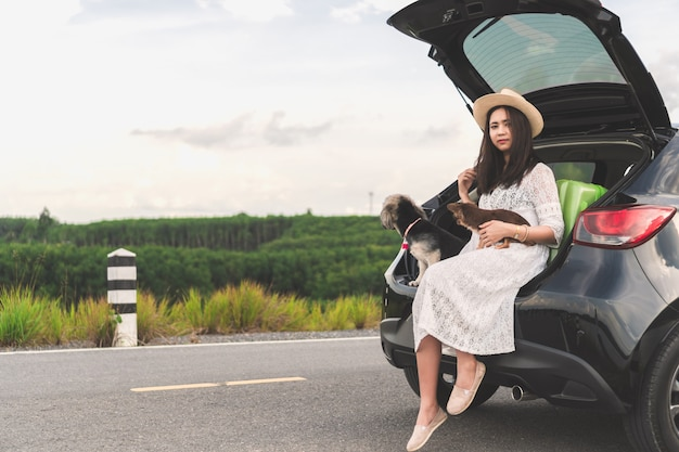 Happy young woman traveler sitting in car with dogs on road and sunset sky. Premium Photo