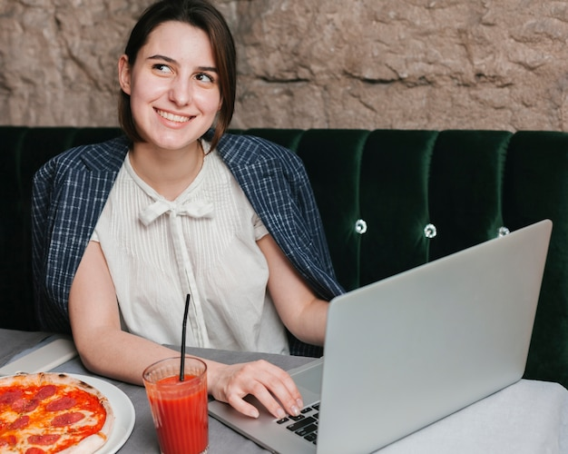 Happy young woman using laptop Free Photo