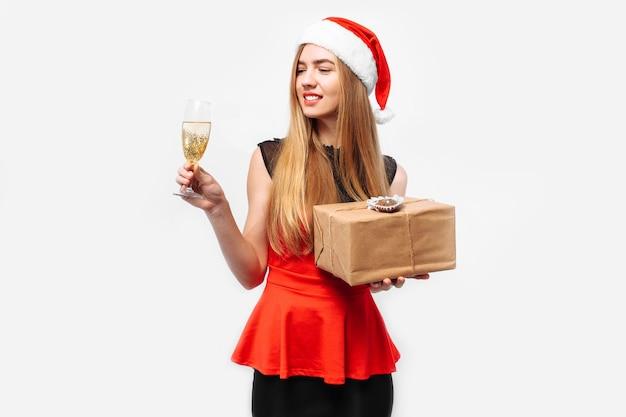 Счастливая молодая женщина в платье и шляпе санта Premium Фотографии