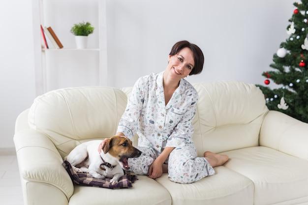 Счастливая молодая женщина в пижаме в гостиной с елкой. концепция праздников. Premium Фотографии