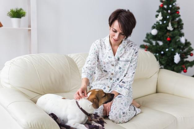 Счастливая молодая женщина в пижаме в гостиной с елкой Premium Фотографии