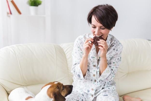 Счастливая молодая женщина в пижаме с прекрасной собакой в гостиной с елкой. каникулы Premium Фотографии