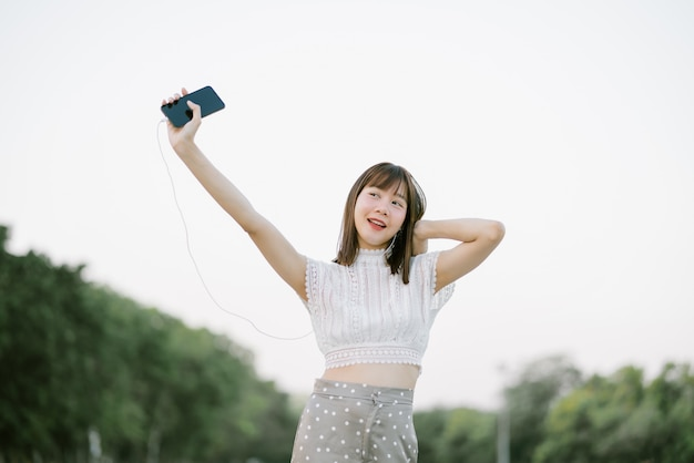 Happy young woman in white clothes with earphones having fun while using mobile phone listening to music with her eyes open looking away from the camera in the park Premium Photo