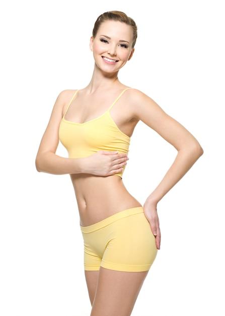 Felice giovane donna con bel corpo sottile in abiti sportivi gialli - isolato sul muro bianco Foto Gratuite