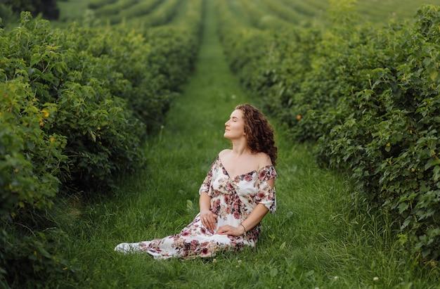 茶色の巻き毛のドレスを着て、庭で屋外でポーズ幸せな若い女 無料写真