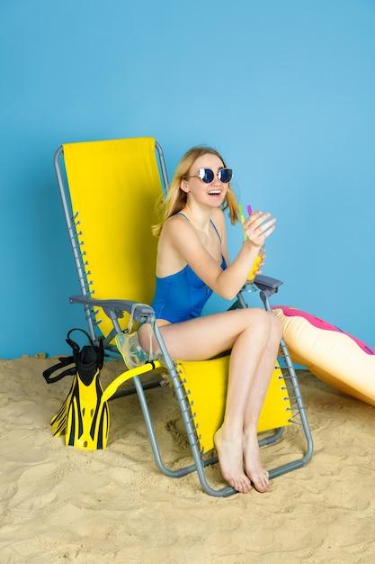 Счастливая молодая женщина с коктейлем, улыбаясь, смеясь, приветствуя на синем фоне студии. понятие человеческих эмоций, выражение лица, летние каникулы, выходные. лето, море, океан, алкоголь. Бесплатные Фотографии