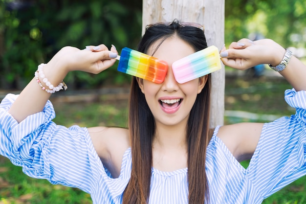 Happy young woman with colorful ice cream in hands in garden. Premium Photo