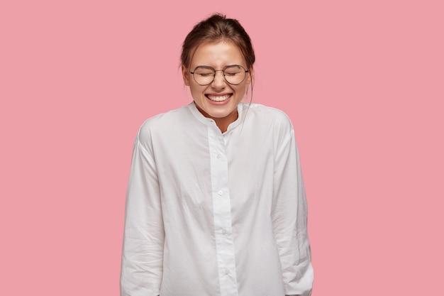 분홍색 벽에 포즈 안경 행복 한 젊은 여자 무료 사진