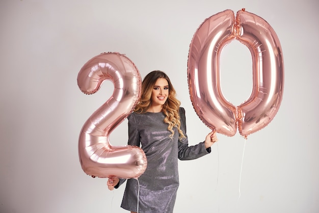Happy young woman with golden balloons celebrating her birthday Free Photo