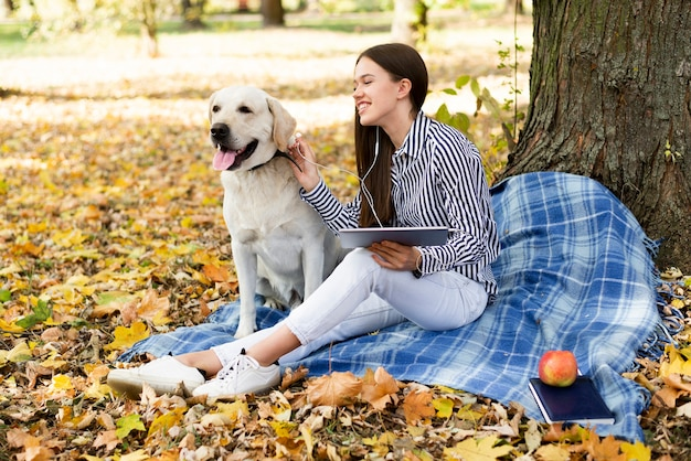 Happy young woman with her dog in the park Free Photo