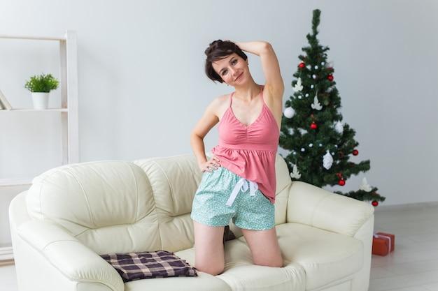 Счастливая молодая женщина с прекрасной собакой в гостиной с елкой. концепция праздников. Premium Фотографии