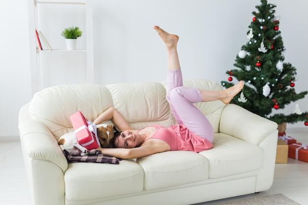 Счастливая молодая женщина с прекрасной собакой в гостиной с елкой Premium Фотографии