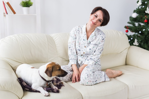 Счастливая молодая женщина с прекрасной собакой в гостиной Premium Фотографии