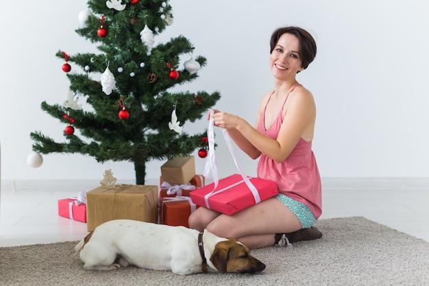 Счастливая молодая женщина с прекрасной собакой открывая настоящую коробку под рождественской елкой. Premium Фотографии