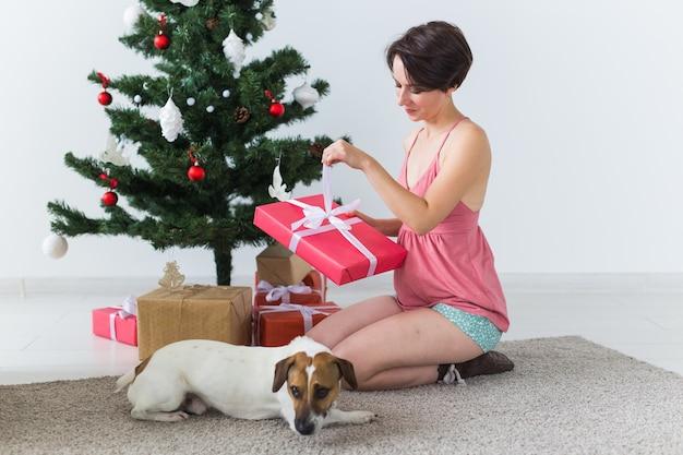 Счастливая молодая женщина с прекрасной собакой открывает подарочную коробку под елкой Premium Фотографии