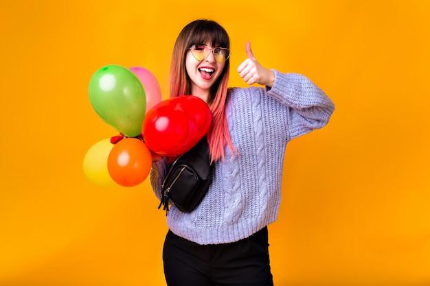 異常なピンクの髪を楽しんで、黄色の壁でポーズをとって、カラフルな誕生日パーティーの風船、カジュアルな流行の服、トーンの色を保持している幸せな若い女性。 無料写真