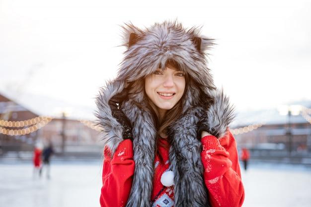 Felice giovane donna con un cappello da lupo in inverno presso la pista di pattinaggio sul ghiaccio si pone in un maglione rosso fuori nel pomeriggio Foto Gratuite