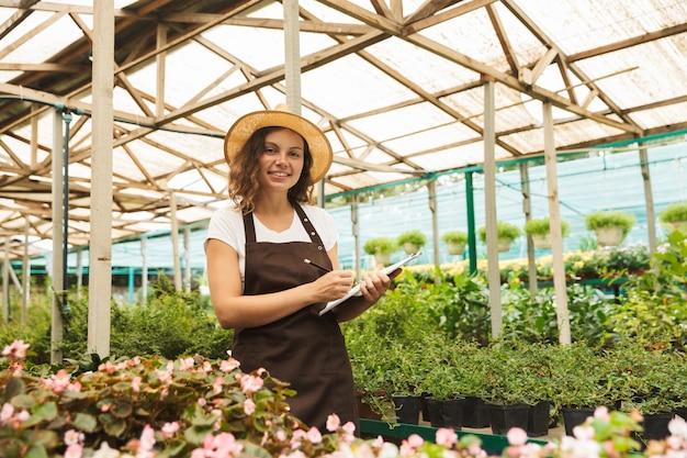 温室で働く幸せな若い女性 Premium写真