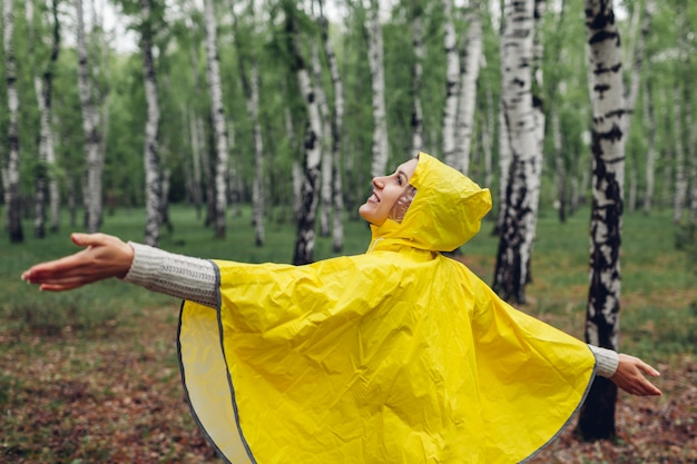 Happy young woman in yellow raincoat walking in spring forest and having fun raising arms Premium Photo