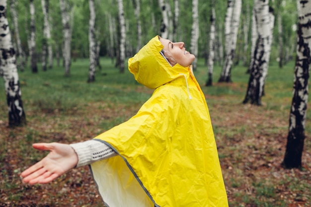 Happy young woman in yellow raincoat walking in spring forest under rain and having fun raising arms Premium Photo