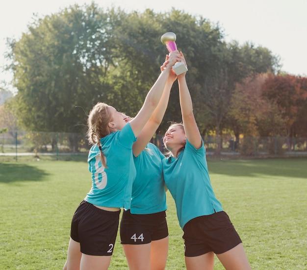 Happy young women raising a trophy Free Photo