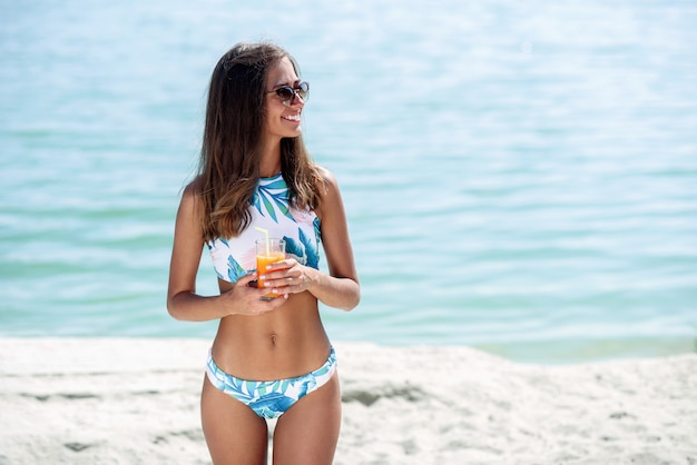 세련 된 선글라스와 해변에서 휴가를 즐기는 패션 비키니에 건강 한 빠져 있 었 단된 몸매와 함께 행복 한 젊은 여성. 해변에서 칵테일 소녀 프리미엄 사진