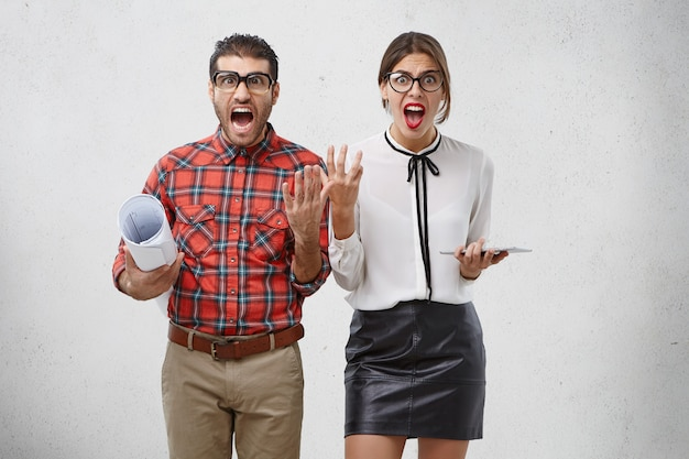 Una coppia furiosa e molestata di designer fa un gesto perplesso e urla in preda al panico Foto Gratuite