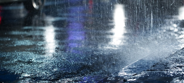 Hard rain fall at night with blurry cars .selective focus. Premium Photo
