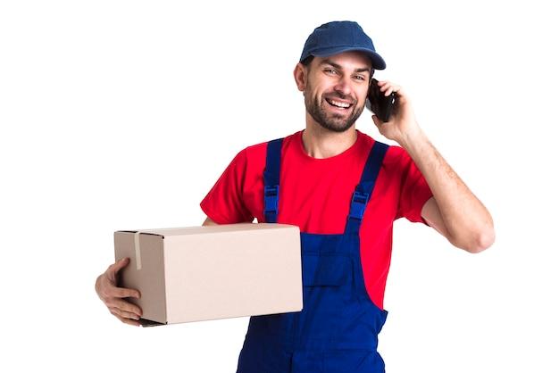 Uomo del corriere del lavoratore duro che tiene una scatola e che parla sul telefono Foto Gratuite