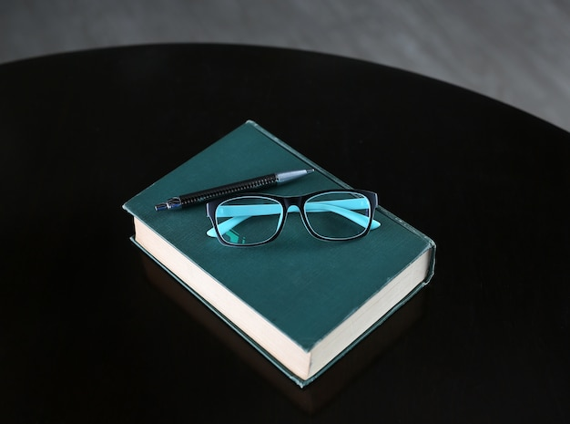 Hardcover book with pen and glasses on wooden table. Premium Photo