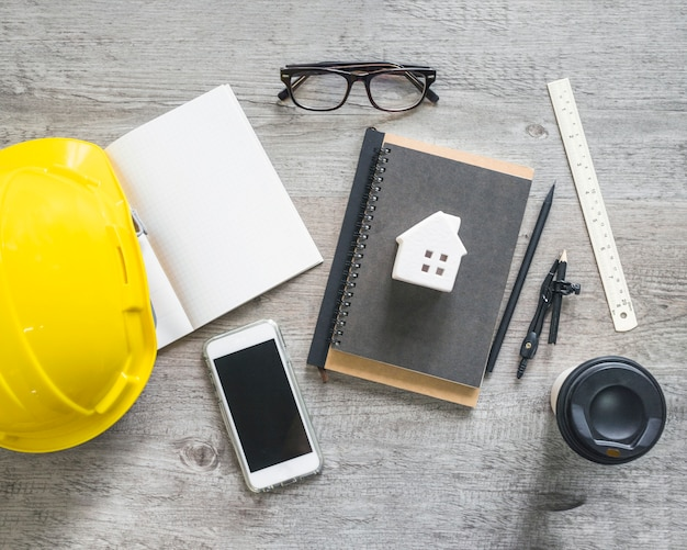Hardhat and stationery near smartphone and cup Free Photo