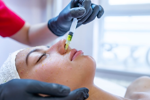 Hardware cosmetology, mesotherapy, portrait of young woman getting treatment of forehead zone Premium Photo