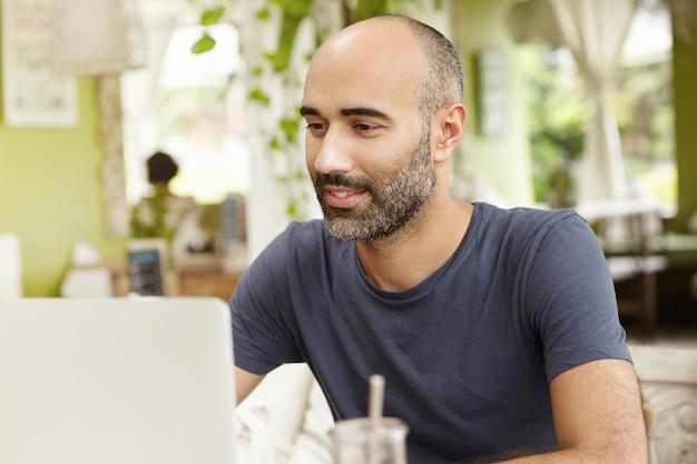 Трудолюбивый мужчина с вдохновенной улыбкой смотрит на экран своего портативного компьютера во время просмотра видео онлайн. Бесплатные Фотографии