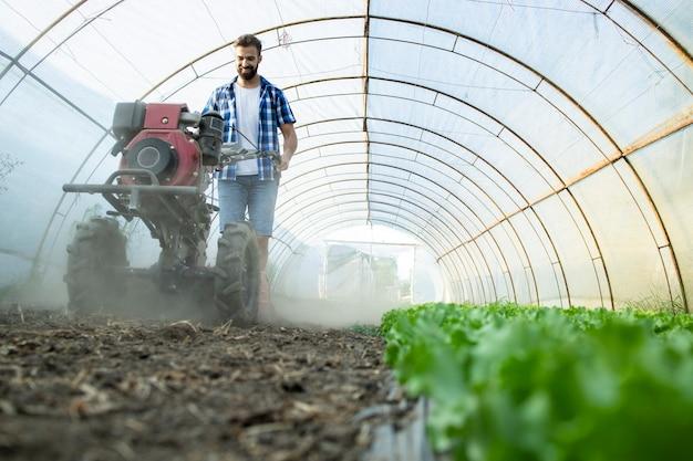 Giovane agricoltore laborioso che aziona il motocoltivatore per preparare il terreno per nuove piantine nell'azienda agricola biologica Foto Gratuite