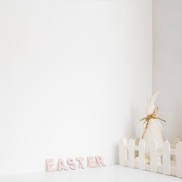 Hare in fence and easter word Free Photo