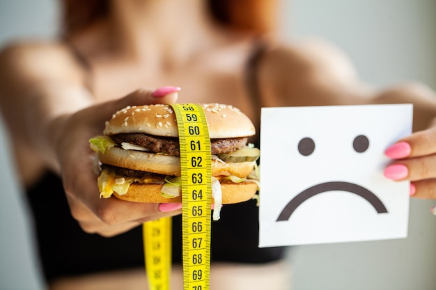 Harmful food. the choice between malicious food and sport. beautiful young girl on a diet. the concept of beauty and health. Premium Photo