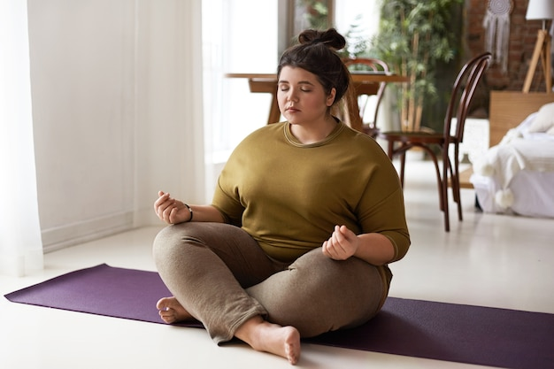 Harmony, balance, zen and peace concept. indoor shot of plus size barefoot young brunette woman with hair bun sitting on mat keeping legs crossed and eyes shut, meditating after yoga practice Free Photo
