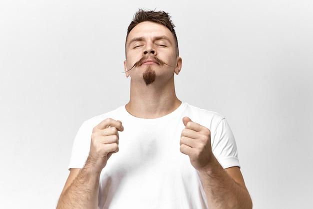Концепция гармонии, мира и баланса. студийный снимок красивого стильного молодого мужчины, одетого в белую футболку, закрывающего глаза, со спокойным довольным выражением лица, медитирующего или слушающего приятную музыку Бесплатные Фотографии