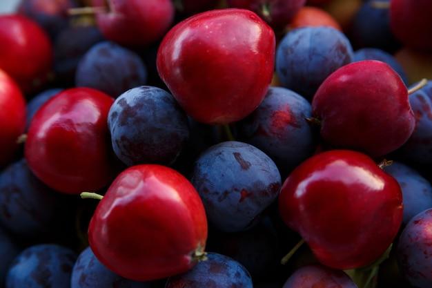 熟した青い梅と赤いリンゴの収穫がクローズアップ Premium写真