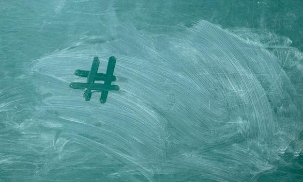 Hashtag it handwritten with white chalk on a green blackboard. Premium Photo