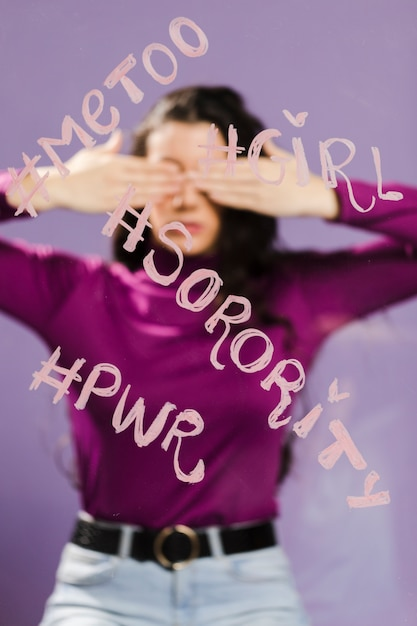 Hashtags words written on a transparent glass and woman covering her eyes Free Photo